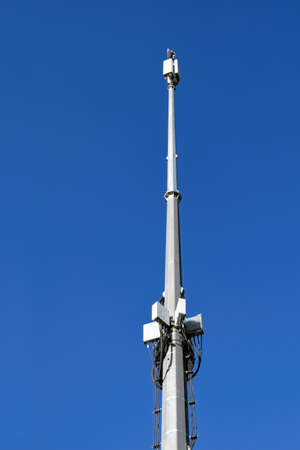 A mast with telecommunication equipment on a background of blue summer sky. Communication towers on blue sky background.