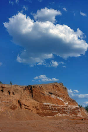 Sand dunes against the blue sky and white clouds. Summer landscape.