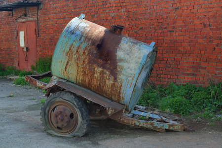 Old rusty tanker truck trailer on red brick wall background.