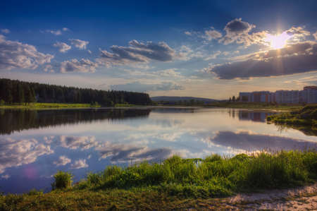 Scenic view of beautiful sunset above the pond at spring evening with cloudy sky background. 免版税图像