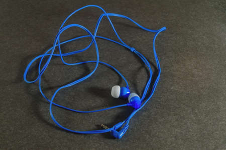 Top view of blue headphones on grey background close-up.