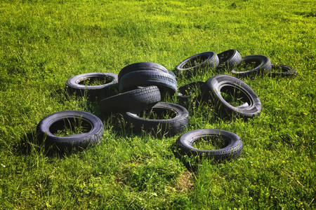 Dump of old used tires on fresh green grass in the forest. The problem of ecology and environmental pollution.