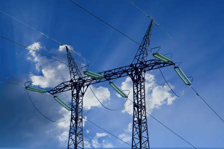 Transmission line of electricity to rural, High voltage electricity pole on bright sky background, electricity transmission pylon.