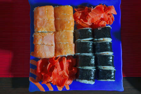 Assorted sushi set background. Different sushi rolls on the table in plates. Close-up.