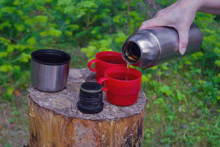 Woman hand pours hot tea out of thermos on summer forest background.