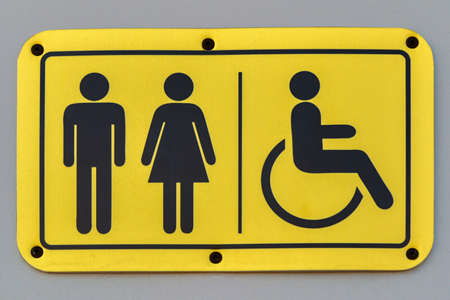 A plate with symbolic images of a man, woman and person in a wheelchair. Stock fotó