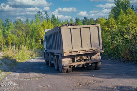 Lorry dump truck rides on a dirt road against the background of the forest and blue sky.