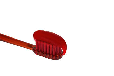 Red toothpaste is on the toothbrush isolated on white background. Dental Care Concept.