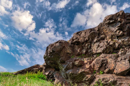 Natural landscape background, bright blue sky with white cumulus cloud. Rock on top of the mountain against the background of a blue summer sky and white cumulus clouds. Stockfoto