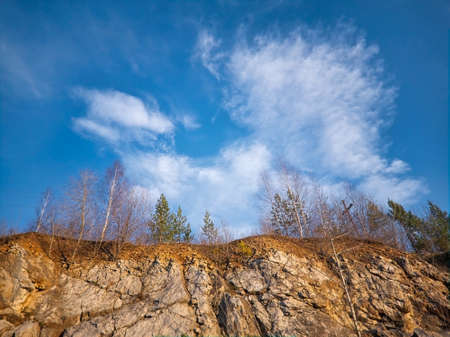Limestone cliffs against a background of blue summer sky and white clouds.