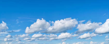 White fluffy clouds in the blue sky. Blue summer sky with white cumulus clouds. Stockfoto