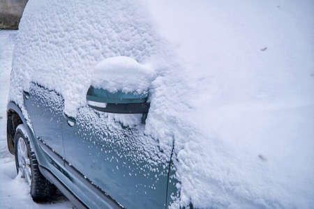 Car under a thick layer of snow. A car covered with a thick layer of snow. Close-up. Winter. Reklamní fotografie