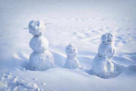 Three comical snowmen made by children on snow in the winter. Stock fotó