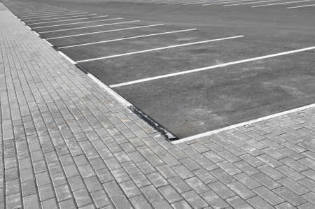 The parking stalls in a parking lot, marked with white lines close-up.