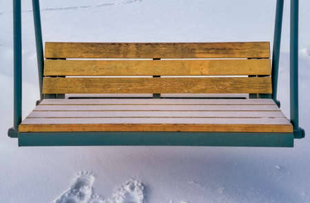 Wooden swing seat in the park in winter close-up. Stock fotó