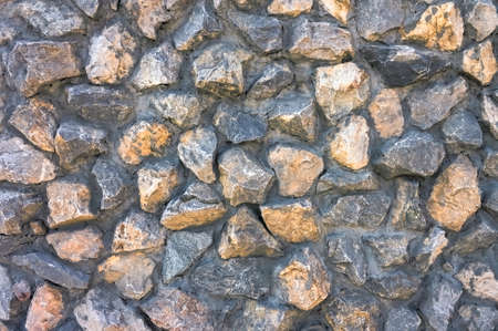 Fragment of the wall. Texture of concrete wall with granite rubble close-up.