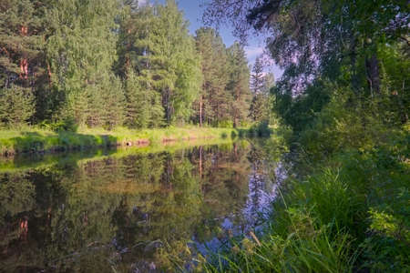 Summer landscape, forest trees are reflected in calm river water against a background of blue sky. Stock fotó