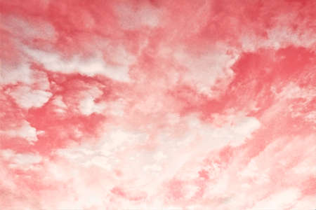 Pink sky background with soft delicate white clouds.