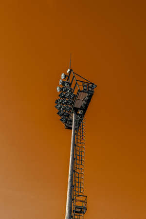 Metal mast with lighting fixtures in the stadium against the orange sunset sky.