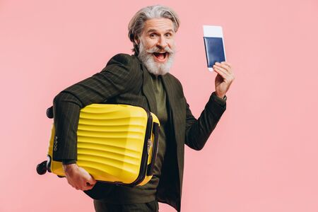 Bearded stylish middle-aged man holding a yellow suitcase and passport with a ticket on a pink background.