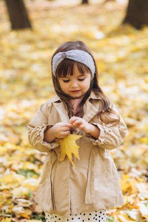 Beautiful little girl in a beige coat in the autumn park