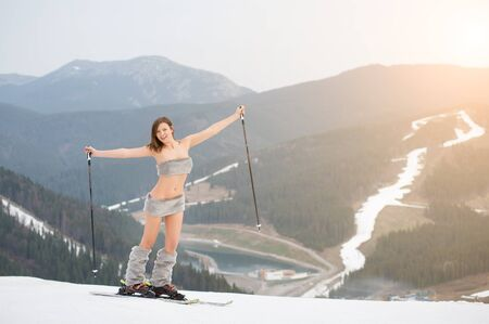 Happy naked female skier standing on the snowy slope of the mountain, rising hands up, wearing ski equipment. Looking to the camera. Ski resort, snowy slopes and forest on background.
