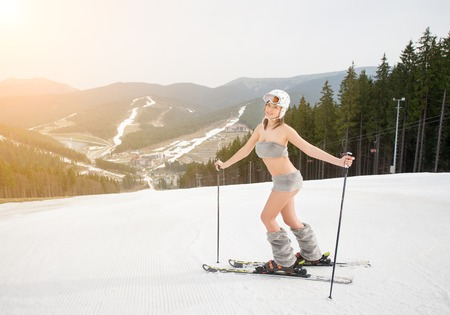 Happy beautiful naked girl skier posing on the snowy slope with ski equipment. Looking to the camera. Ski resort, ski lift, slopes and forest on background Stock Photo