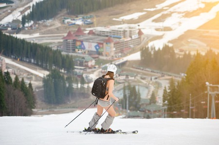 Active female skier skiing on the snowy slope of the mountain, wearing ski equipment, backpack, helmet. Ski resort, ski lift, slopes and forest on background. Spring Stock Photo