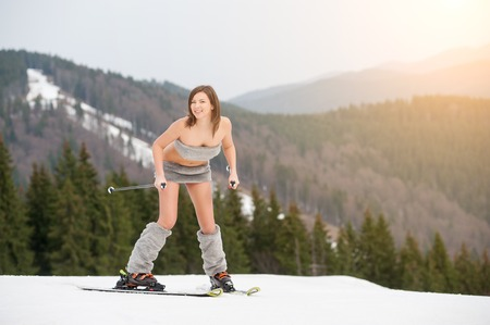 Happy naked girl skier starting skiing on the snowy slope of the mountain, wearing ski equipment. Looking to the camera. Forest on background. The end of winter season