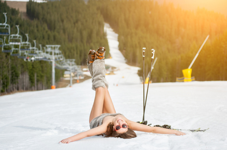 Young happy naked skier is having fun on snowy slope near ski lift at ski resort. Active woman is wearing sunglasses, boots. The end of winter season Stock Photo