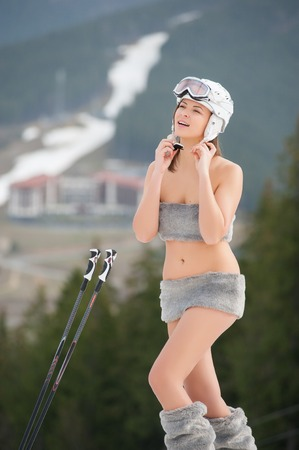 Portrait of naked female skier. Happy girl is smiling and putting on helmet. Ski resort, slope and forest on background