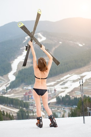 Back view of unrecognizable sexy female skier is standing on the slope and holding skis above head. Wearing swimsuit, boots. Ski resort, mountains, snowy slopes, forests on the background Stock Photo