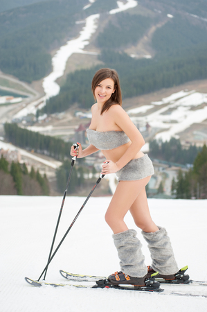 Full length portrait of smiling sexy woman skier standing on the snowy slope of the mountain. Looking to the camera. Ski resort, slopes and forests on background. Bukovel, Ukraine