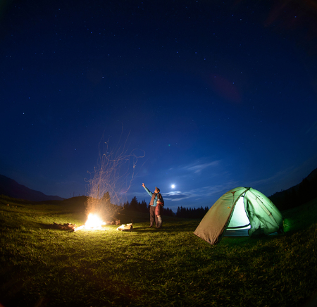 Father and son standing near big campfire and tent looking at beautiful night sky full of stars and enjoying night scene. Man is pointing at the sky