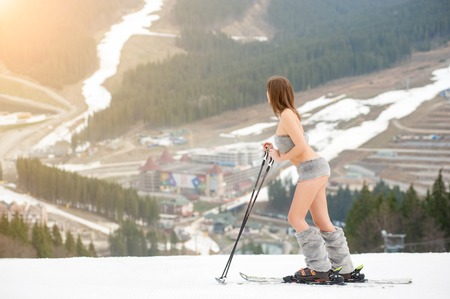 Naked woman skier standing on the snowy slope of the mountain, wearing ski equipment. Ski resort, slopes and forest on background. Spring is coming. Bukovel, Ukraine