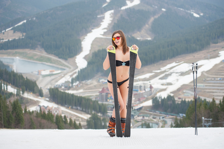 Smiling active sexy woman is standing on the top of the slope with skis. Wearing swimsuit, boots and sunglasses. Ski resort, mountains, snowy slopes, forests on the background. Winter holiday