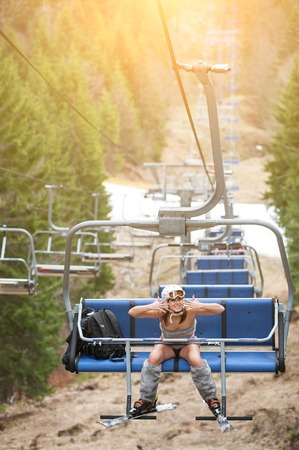 Happy girl skier is sitting on ski lift and riding up to the top of the mountain with ski equipment. Mountains, snowy slopes, forests on the background. Ski resort. The end of winter season Stock Photo