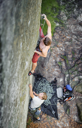 Young rock climber hooking rope at beginning of route, male belayer watching him. Outdoor summer day Stock Photo