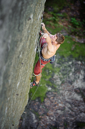 Young man climbing on rock cliff securing carbines and rope. Outdoor summer day. Focus is on a hand