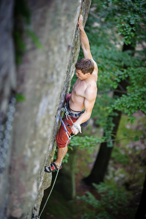 athletic man climbing on rock cliff securing carbines and rope. Outdoor summer day