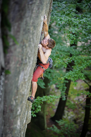 Athletic young rock climber climbs on overhanging cliff in summer time