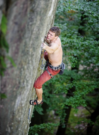rockclimber: Muscular rock climber climbs on overhanging cliff in summer time Stock Photo