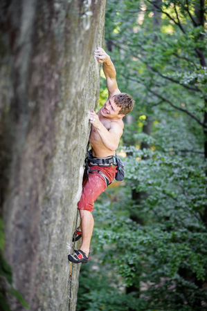 Young focused rock climber climbing up a steep rocky wall in summer time