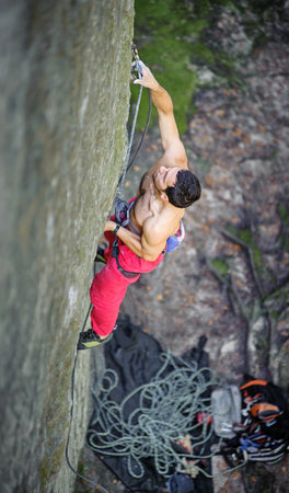 Muscular rock climber climbs on large boulders with rope engaged. Outdoor summer day