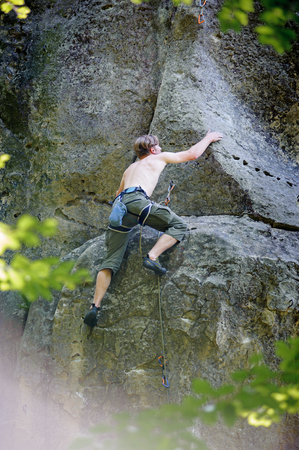 Young man climbing on large boulders outdoor summer day