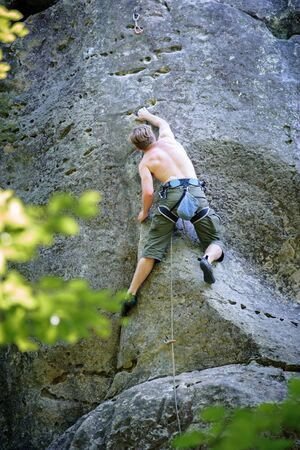 Athletic young male climber climbing on large boulders. outdoor summer day