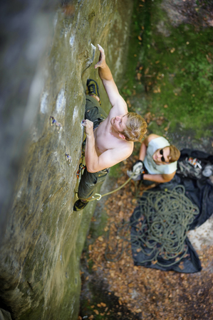Athletic young male climber searches for handholds while climbing on large boulders. Partner standing on the ground belaying the climber. Outdoor summer day