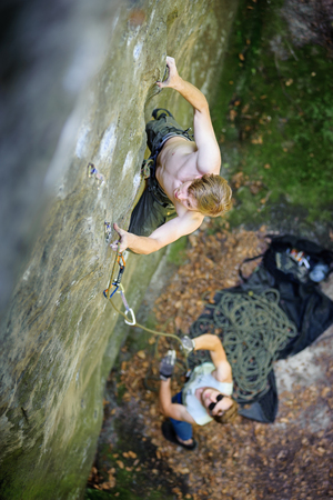 Young man lead climbing on large boulder securing carabiners and rope. male partner belaying. Outdoor summer day