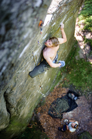 Young man rock-climbing on large boulder, holding one hand in bag with powder chalk magnesium. his partner belaying. Outdoor summer day