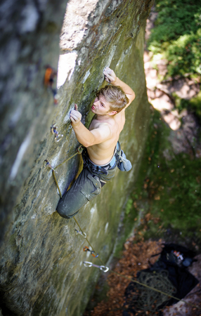 Young athletic man rock-climbing on large boulders. Outdoor summer day